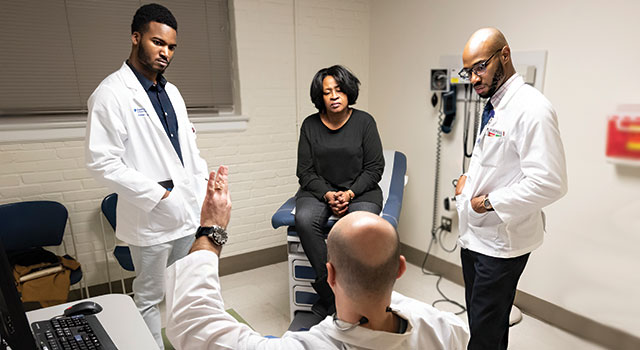 Duke students Rafeal Baker (left) and Nathaniel Neptune (right) listen as family nurse practitioner Virgil Mosu discusses a patient's diagnosis