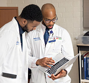 Students Rafeal Baker (left) and Nathaniel Neptune (right) review a patient's chart before an exam.
