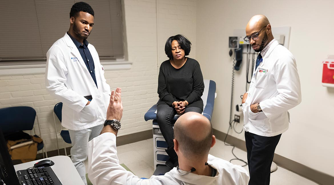 Duke Students Rafeal Baker (left) and Nathaniel Neptune (right) listen as family nurse practitioner Virgil Mosu discusses a patient's diagnosis.