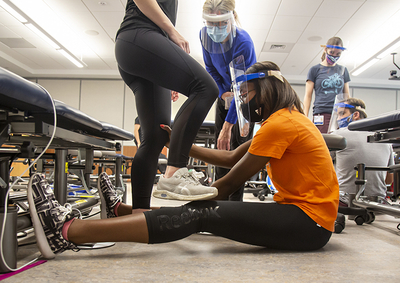 Glenda Holcomb, a second-year Doctor of Physical Therapy student, practices leg stretching with a fellow student during a pediatric physical therapy class under the instruction of Laura Case, PT, DPT, MS, center. Photo by Shawn Rocco.