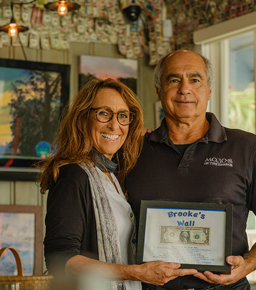 "Andrea and John Pitera hold the ""Brooke's Wall"" plaque containing the first dollar bill given by Brooke Williams"
