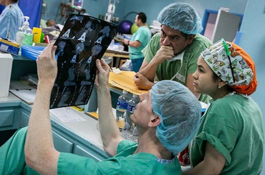 Duke surgeon Adam R. Williams examines chest x-rays with Honduran surgeon Hugo Orellana and Marysol Valeriano, MD.