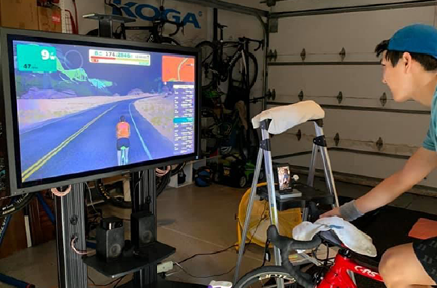 Justin Koga, a senior political science, history, and statistics student, rides virtually at his home in Irvine, California.